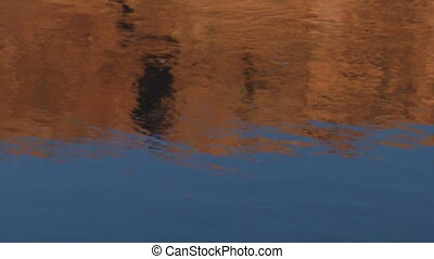 red rock cliffs reflected in water on the Colorado River