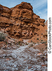Red Rocks Sit Above White Mineral Covered Wash