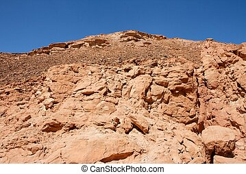 Red rocky hill in the desert landscape