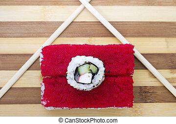 red rolls with chopsticks on a cutting board