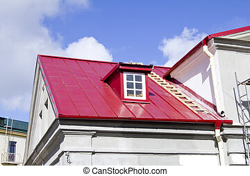 Red roof with gutter system, ladder and attic on sky fon