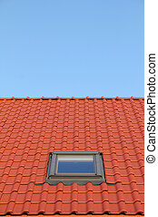 Red roof with one vertical windows and blue sky