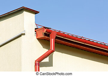 red rooftop gutter with downspout - corner of a house with...
