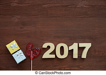 Red rooster, symbol of 2017 on the Chinese calendar. Lollipop in the form of a red rooster on a dark wooden background