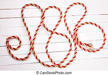 Red rope on a white background wooden table