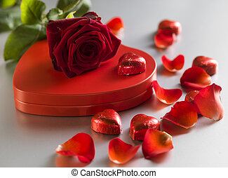 Red rose and box with red hearts on a white background