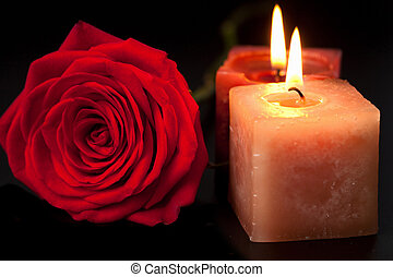 red rose and candles over black background