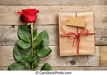 Red rose and gift box with tag on wooden background