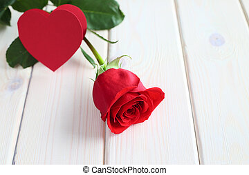 Red rose and paper heart