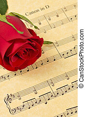 Red Rose Bud on Sheet Music - A red rose bud rests on...