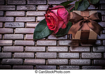 Red rose giftbox on wicker wooden place mat