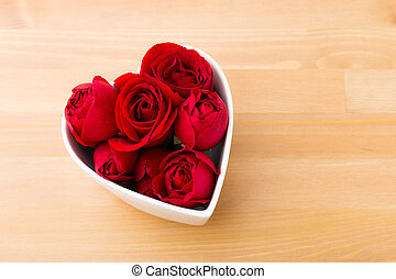 Red rose inside the heart shape bowl on wooden background