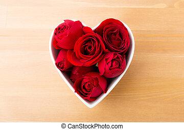 Red rose inside the heart shape bowl