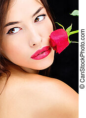 Red rose near lips and naked shoulder