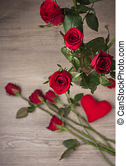 Red rose on old wood background (top view)