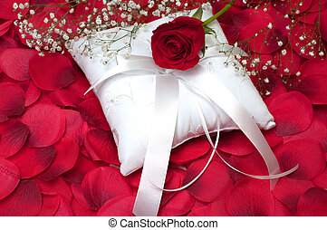 Red rose with baby's breath on white ring bearer's pillow with red rose petals.