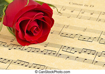 Red Rose on Sheet Music - A red rose bud rests on...