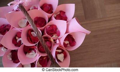 Red rose petals in pink bags at basket