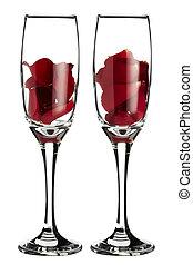 Red rose petals inside 2 champagne glasses