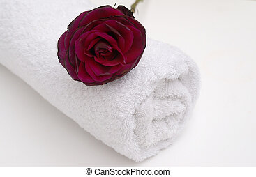 romantic spa with white towel and red rose