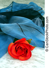 Red rose with a blue scarf