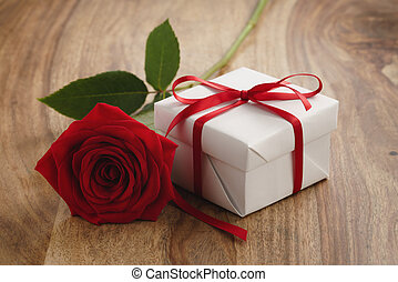 red rose with gift box on wooden table