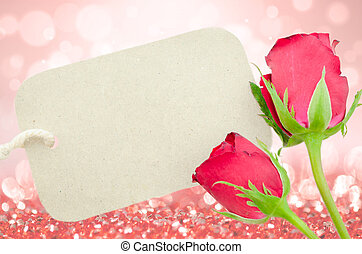 Red roses and blank paper tag for your text.
