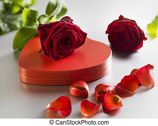 Red roses and box with red hearts on a white background
