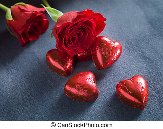 Red roses and chocolate hearts on a dark blue background