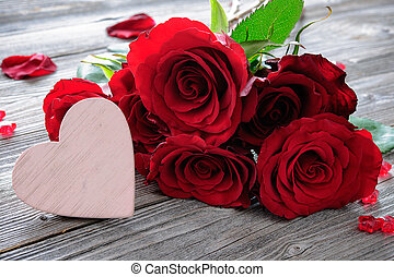 Red roses and heart on wooden background