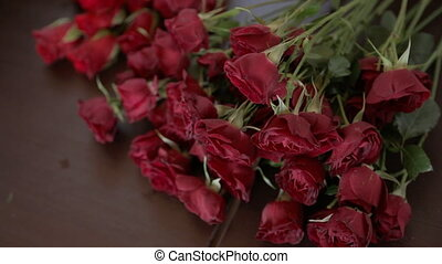 Red roses and pink chrysanthemums lie on table in workshop....