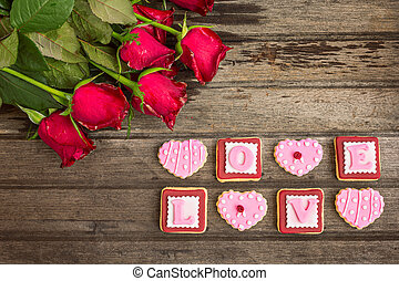 Red roses and pink cookies in shape of LOVE word, on wooden background, top view
