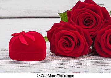 Red roses and velvet gift box.