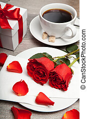 red roses, cup of coffee and present