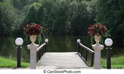 Red roses flowers composition bouquets at wedding ceremony at countryside at summer sunny day