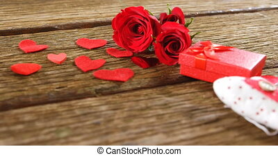 Red roses, gift box and heart shapes on the wooden surface 4k