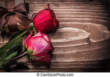 Red roses giftbox on wooden board holidays concept