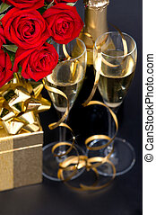 red roses, golden gift and champagne