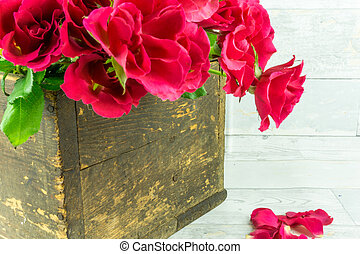 Red roses in a rustic wooden crate