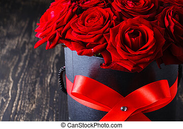 Red roses in box on dark background