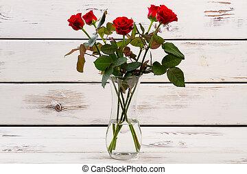 Red roses in glass vase.