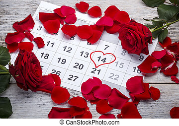 Red roses lay on the calendar with the date of February 14