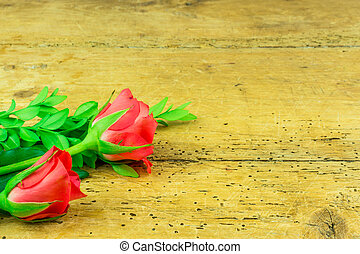 Red roses on a rustic wood background