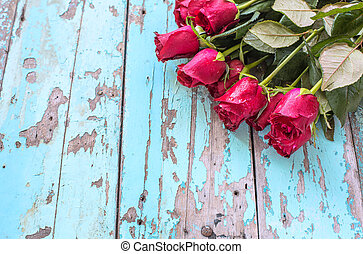 Red roses on old blue wooden background