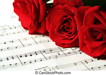 Red Roses on Sheet Music - Three red roses resting on sheet...