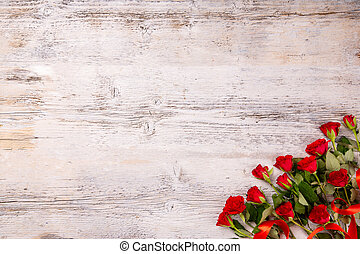 Red roses on white wooden table