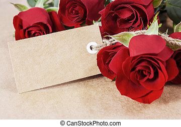 Red roses with blank paper tag on brown paper
