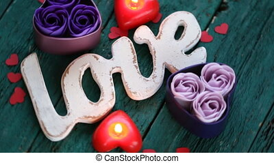 Red roses with heart shape and candles on wooden background. Valentines day concept. Love and romance