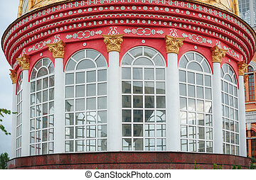 Red round building with large Windows and columns