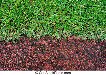 red running track and green grass in stadium